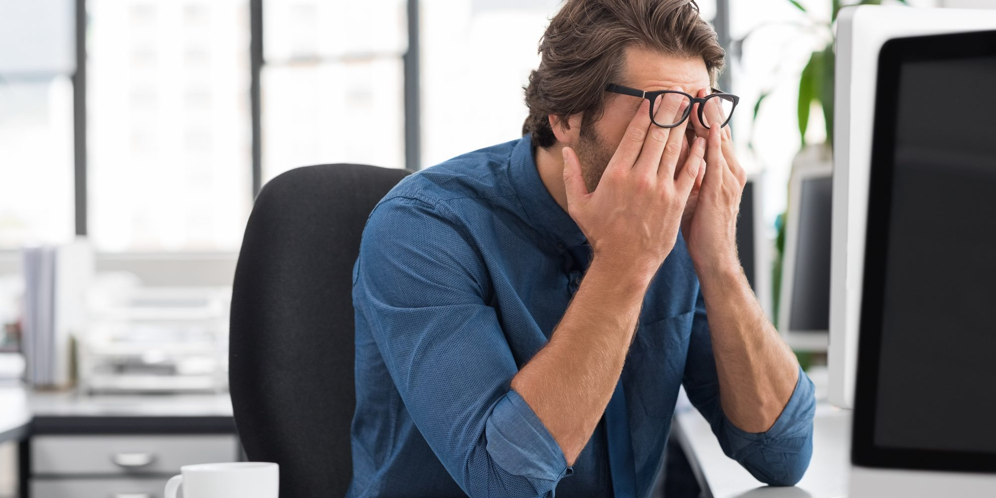Portrait of an upset businessman at desk in office. Businessman being depressed by working in office. Young stressed business man feeling strain in eyes after working for long hours on computer.